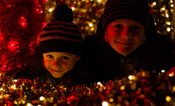 Children smile amongst Christmas tinsel.