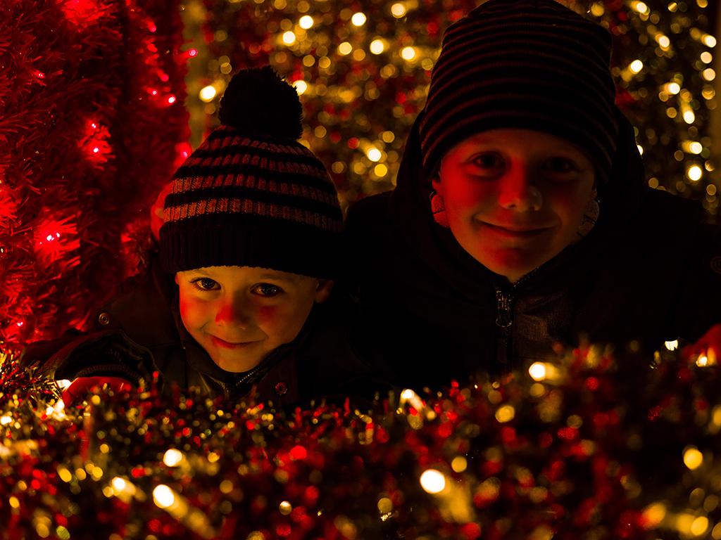 Children smile amongst Christmas tinsel.