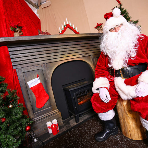 Father Christmas sits next to a fire.