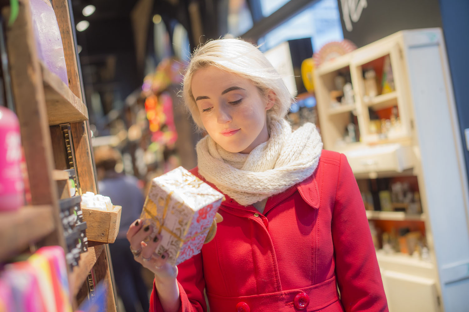 A young lady examines a Christmas gift in Lush, Bournemouth.
