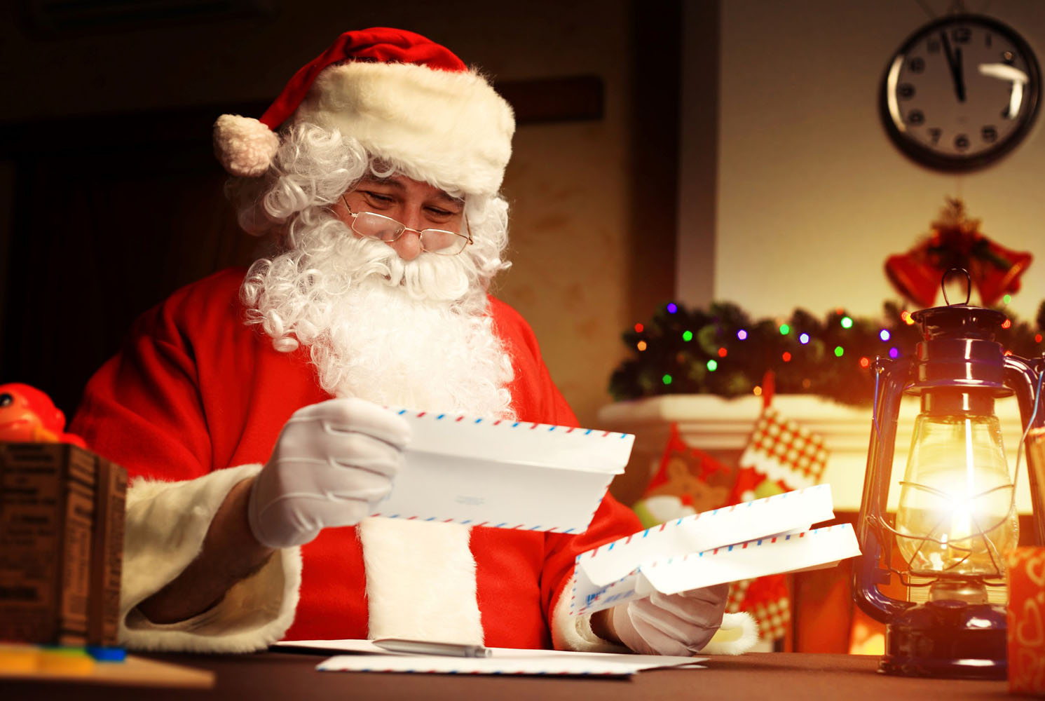 Father Christmas studies air mail letters next to a lantern.