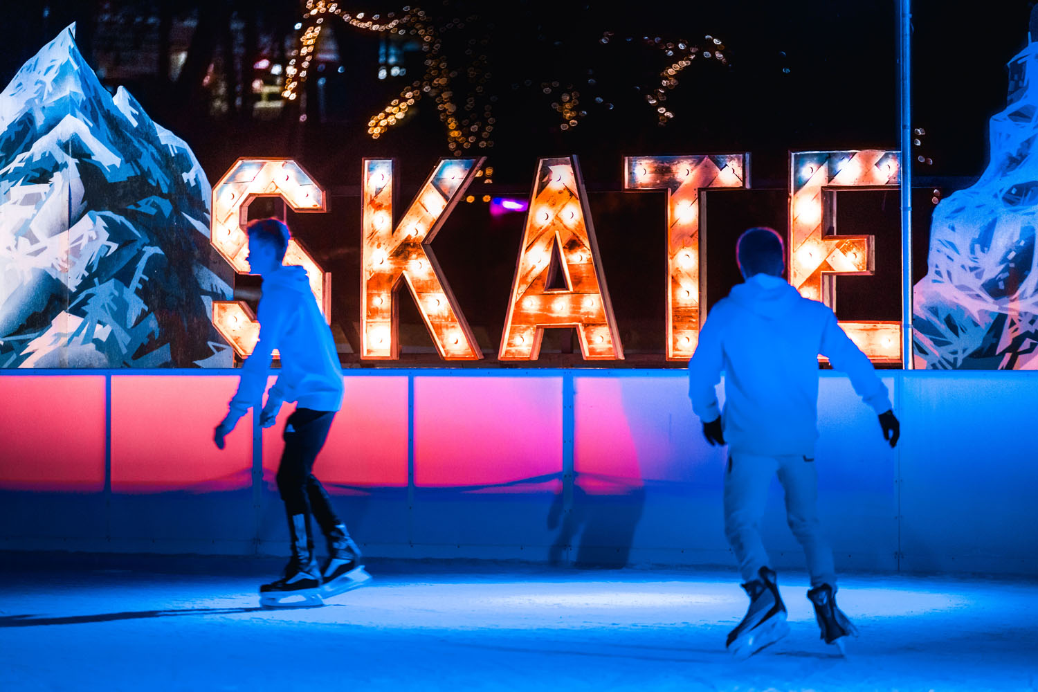 Large illuminated SKATE letters at an outdoor skating rink.