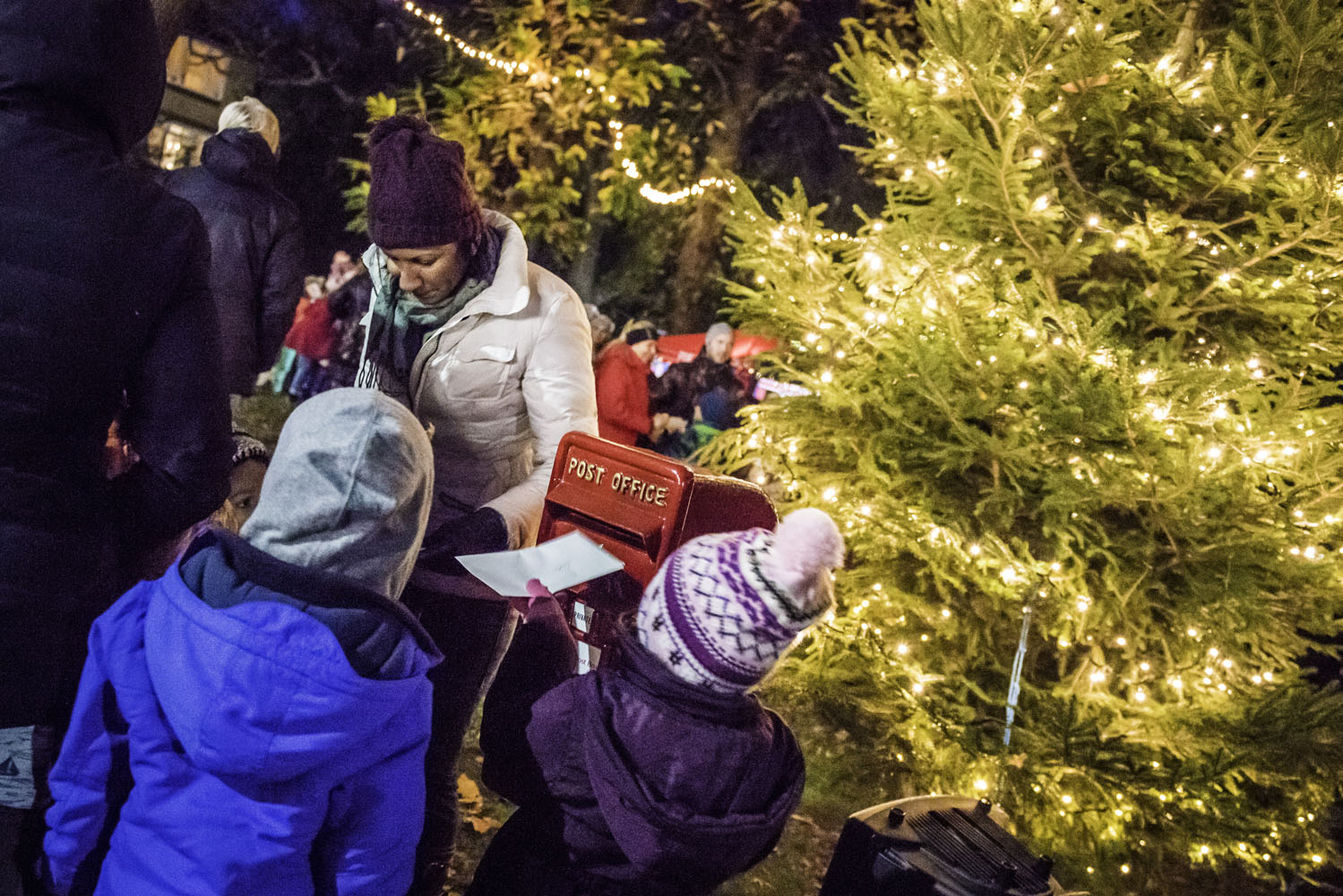 Children post letters in an old fashioned letterbox next to an illuminated Christmas Tree.