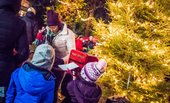 Children post a letter to Santa in a post box next to a Christmas tree.
