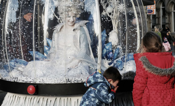 A lady dressed as a snow queen site in a giant snow globe whilst two children laugh.