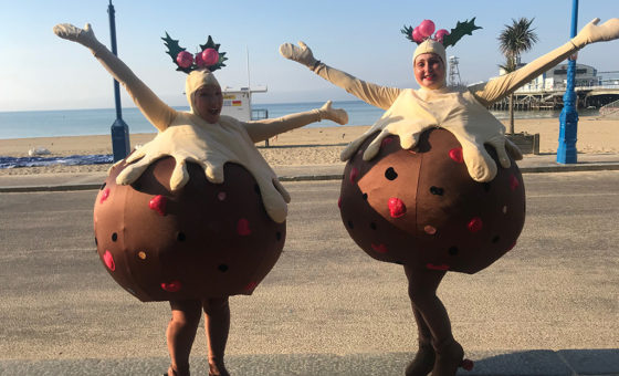 Two ladies dressed as roller skating Christmas puddings on Bournemouth sea front.