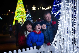 Family laughing and smiling around the Tree of light near Bournemouth beach