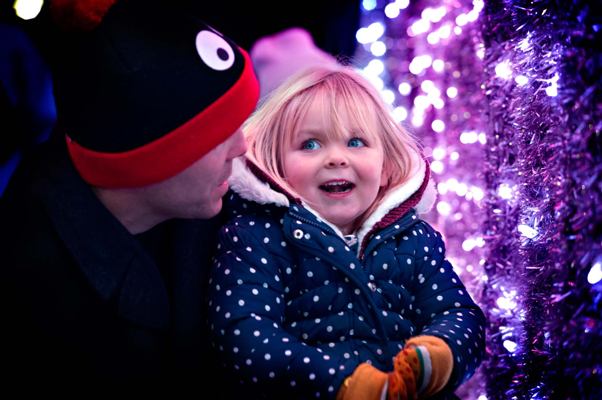 Girl and her father interacting with the Christmas lights