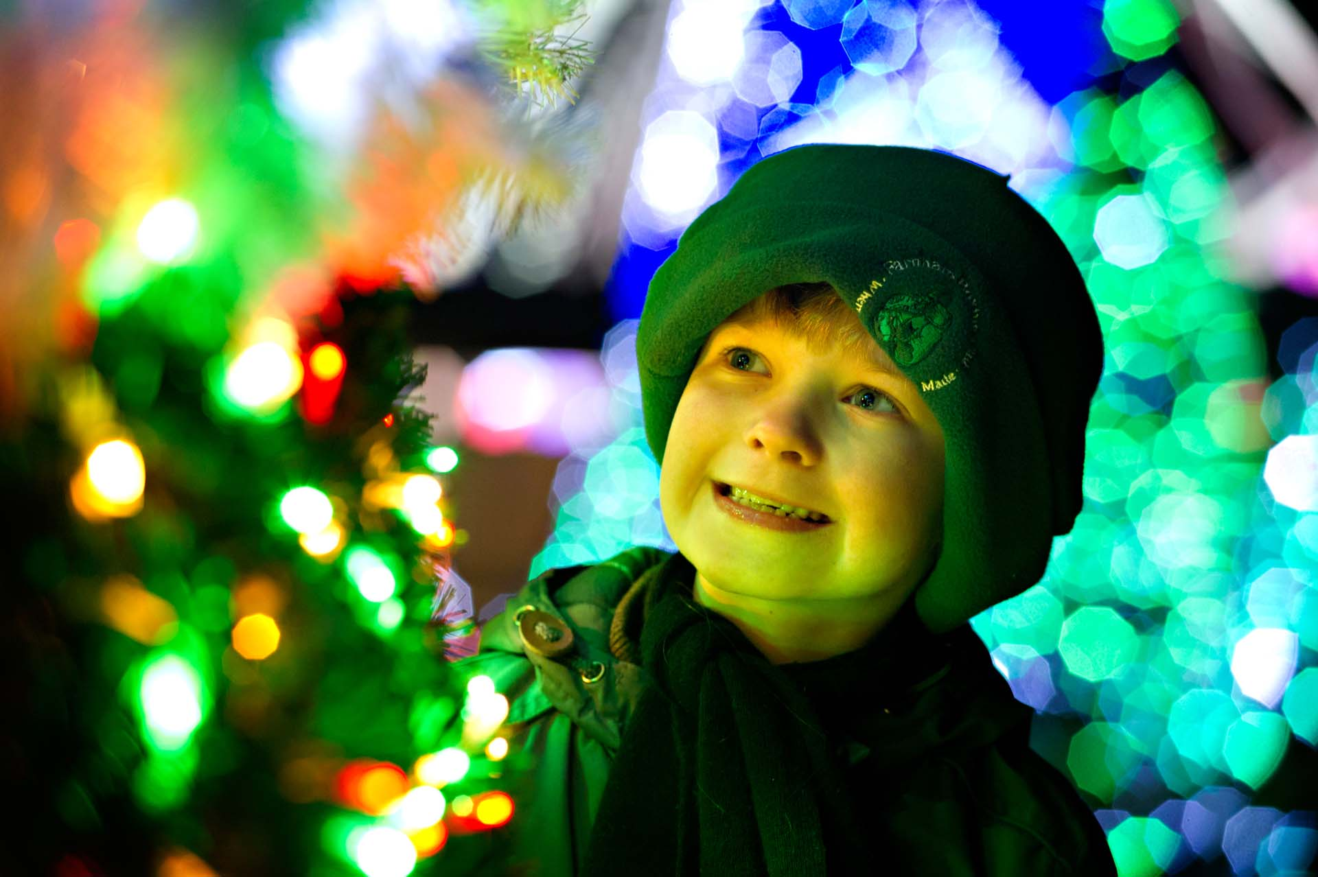 Child in hat smiling at the Christmas tree lights