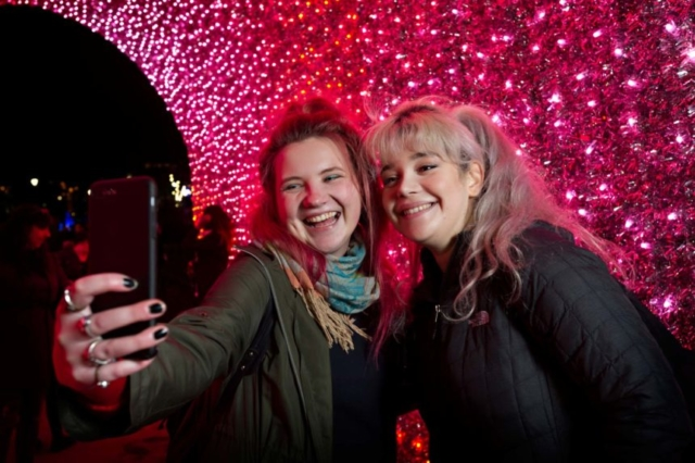 Two young girls snapping a selfie under the feature tree