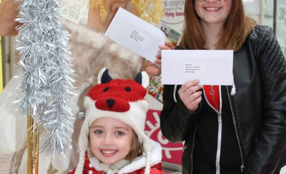 Christmas fairy and visitors holding up their postcards to Santa